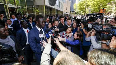 Majak Daw surrounded by reporters and photographers outside the County Court.