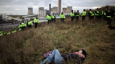 A British anti-coal power protester sleeps as police officers form a line during a climate change demonstration at Ratcliffe Power Station in England.