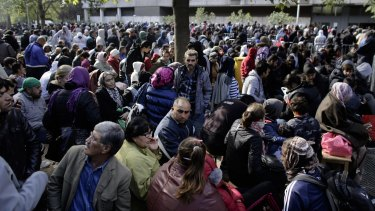 Hundreds of migrants and refugees wait for Berlin's State Office of Health and Welfare in Berlin, Germany, last year.