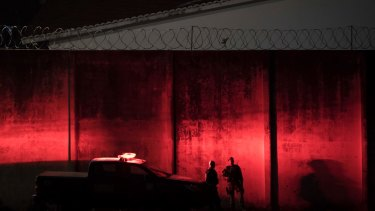 Police stand guard outside the Alcacuz prison amid tension between rival gangs at dusk in Nisia Floresta, near Natal, Brazil.