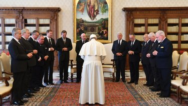 The Grand Master of the Knights of Malta, Giacomo Dalla Torre del Tempio di Sanguinetto, 7th from left, and his delegation are led in prayer by Pope Francis during a private audience at the Vatican in June.