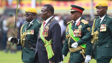 Emmerson Mnangagwa, second left, with coup-leader Army General Constantino Chiwenga, second right, inspects the military parade after being sworn.