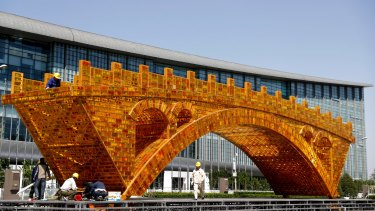 Workers install a 'Golden Bridge of Silk Road' structure outside revealed at the time of China's Belt and Road Forum in Beijing in April.