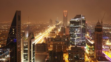 The kingdom Tower, centre rear, stands illuminated by light as  traffic moves along the King Fahd highway in Riyadh.
