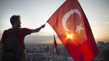 A protester waves the Turkish flag from a rooftop at Istanbul's Taksim Square in June 2013.