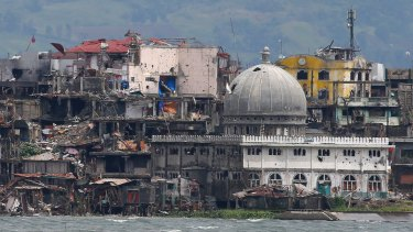 A mosque with its dome blasted out with holes is among destroyed buildings in battle-scarred Marawi,Philippines.