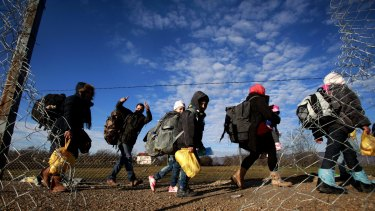 Refugees walk towards the border with Serbia from the transit centre for refugees near the northern Macedonian village of Tabanovce.