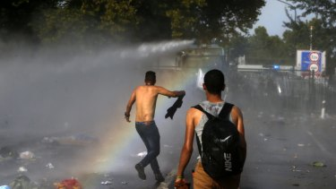 Hungarian police spray water on migrants at the border crossing with Serbia.