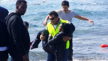 A man carries a migrant from the Aegean sea, in the eastern island of Rhodes.
