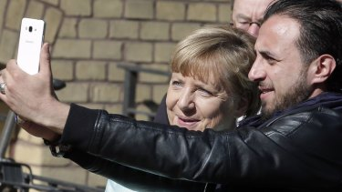 An unidentified man takes a selfie with Angela Merkel, left, during her visit at a migrant registration centre in Berlin in September.