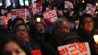 Thousands of South Koreans hold signs during a rally calling for President Park Geun-hye to step down on Saturday.
