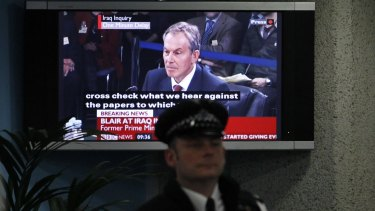 A police officer stands in front of a television screen in the foyer of the venue hosting the Chilcot Inquiry in London in 2010. The inquiry's conclusions have still not been released.