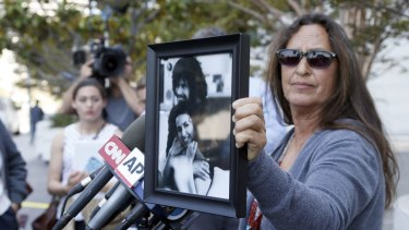 Janet Wolfe holds a photo of her brother Randy Wolfe, better known as Randy California, a member of the band Spirit outside US federal court on Thursday in LA.