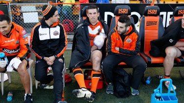 Braith Anasta of the Tigers sits on the bench with an ice pack on his left arm during the NRL match between the Wests Tigers and the Penrith Panthers in July 2014.