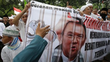 Protesters hold a banner calling for the arrest of  Ahok, depicted with fangs and horns, outside City Hall in Jakarta.