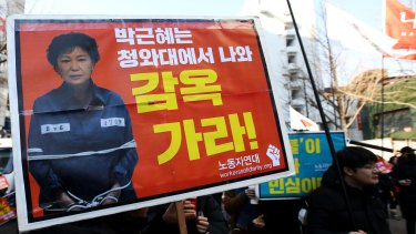 A demonstrator demanding South Korean President Park Geun-hye's impeachment holds a sign featuring a photograph of Park during a protest on Friday.