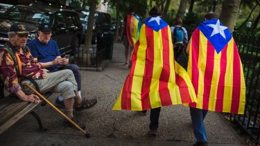 Two men watch pro-independence supporters passing by as they gather in support for the secession of the Catalonia region from Spain outside the United Nations headquarters in New York on Wednesday.