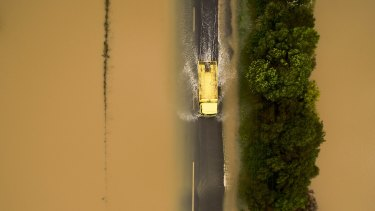 A yellow truck drives through flood waters after heavy rain caused flooding near Clevedon.