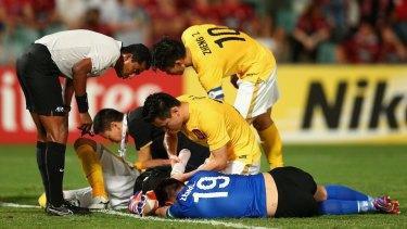 Zeng Cheng of Guangzhou receives attention during the Asian Champions League match between the Wanderers and Guangzhou Evergrande.