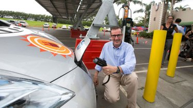 Tony Gilding, owner of the Macadamia Castle, charges an electric car at a new solar panel charging station.