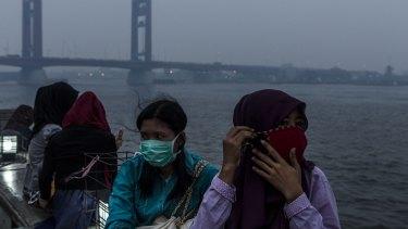 Wearing faces masks in Palembang, Indonesia, as haze shrouded the Ampera bridge on the weekend.