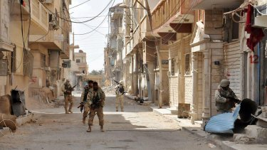 Syrian government soldiers patrol a street in the ancient city of Palmyra, central Syria, in March.