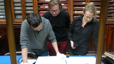 The artists view old master prints in the Museum of Archaeology and Anthropology as part of the Antipodes project.