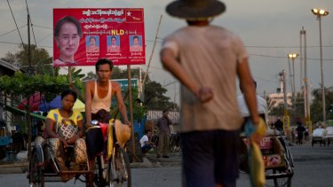 A man rides a rickshaw in the foreground of a billboard promoting candidates of  Myanmar's opposition leader Aung San Suu Kyi's National League for Democracy party in Yangon on Wednesday.