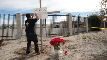 A cross and a sign outside the police perimeter around the Inland Regional Centre, the site of a mass shooting that left 14 dead and 21 wounded, in San Bernardino, California.
