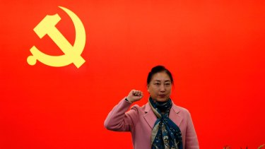 A woman poses for a photograph in front of a Communist flag on display in Shanghai, China.
