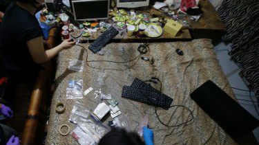 Members of the Philippines' National Bureau of Investigation and the FBI gather evidence at Deakin's residence. Authorities have since arrested three women who were livestreaming sexually exploitative videos of girls to men paying by the minute to watch from countries including Australia.
