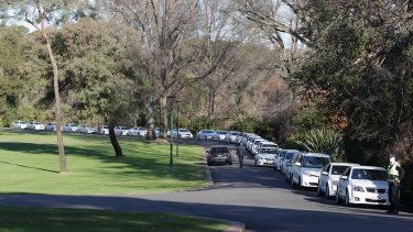 Comcars wait to pick-up the politicians after a swearing-in ceremony at Government House.