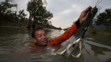 Laotian fisherman Siett Chanthasounthone collects fishing nets set the previous evening.