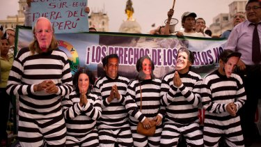 People wearing masks of Peruvian politicians pretend to be prisoners during a protest calling for justice after the Odebrecht corruption scandal in Lima, Peru,.