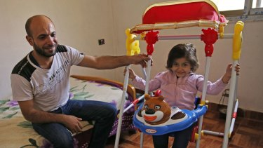 Abdul Halim al-Attar, a refugee from Syria sits next to his daughter Reem, 4, at his house in Beirut.