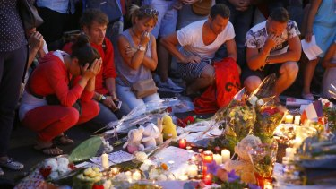 People pay homage to the victims at a makeshift memorial in Nice.
