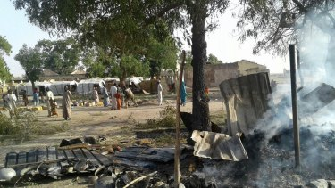 In this image supplied by the aid group Medecins Sans Frontieres, smoke rises from a burnt-out shelter at a camp for displaced people in Rann, Nigeria.