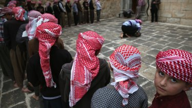 Yazidi boys line up to pray at their religion's most holy temple on November 6, in Lalish, Iraq. Many Yazidi visitors to the Lalish temple were displaced from Sinjar Mountain, overrun by IS in 2014, when IS killed thousands of the men and enslaved many Yazidi women.