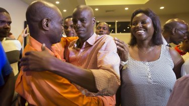Presidential candidate Jovenel Moise, centre, from the PHTK, greets a supporter accompanied by his wife Martine, right.