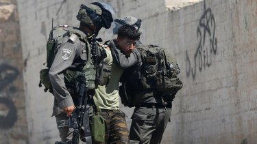 Israeli border police arrest a Palestinian  in the occupied West Bank village of Deir Abu Mashal  on Saturday.