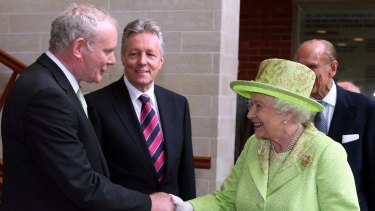 The Queen shakes hands with Martin McGuinness, watched by then first minister Peter Robinson, centre, at the Lyric Theatre in Belfast in June 2012.