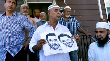 Worshippers outside the Ozone Park mosque hold a police sketch of a suspect wanted over the shooting of two men.