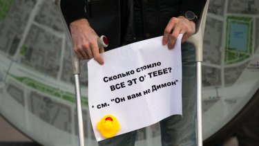 A man holds a poster with a yellow duck toy in Moscow over the weekend.