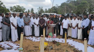 Sri Lankan ethnic Tamil political activists observe silence near a makeshift monument, where thousands of people were killed in fierce fighting between the army and Tamil Tiger rebels.