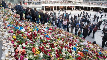 People leave flowers on the steps at Sergels Torg following Friday's attack in central Stockholm, Sweden.