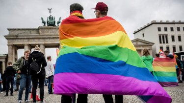 Men with rainbow flags stand in front of the Brandenburg Gate to celebrate the legalisation of same-sex marriage in Berlin on June 30.