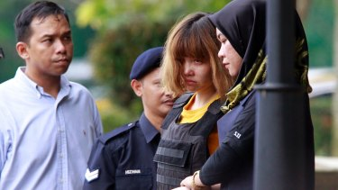 Vietnamese murder suspect Doan Thi Huong, second from right, is escorted by police officers out of Sepang court in Malaysia on Wednesday.