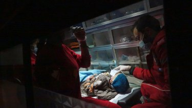 A severely ill child is evacuated by ambulance by Syrian Arab Red Crescent emergency workers.