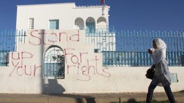A woman walks past graffiti in Sidi Bouzid, Tunisia.
