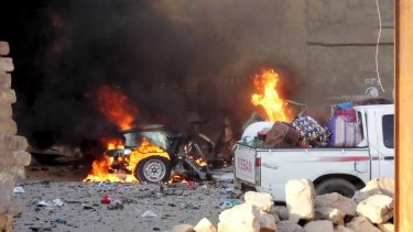 A car is engulfed by flames during clashes in Ramadi.